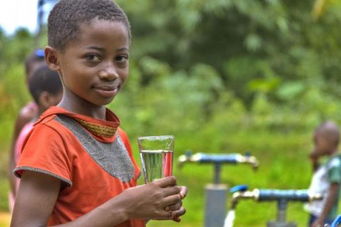 Child holding a glass of clean water